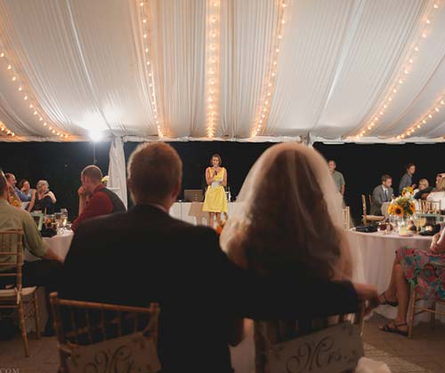Bridesmaid giving a speech at event.